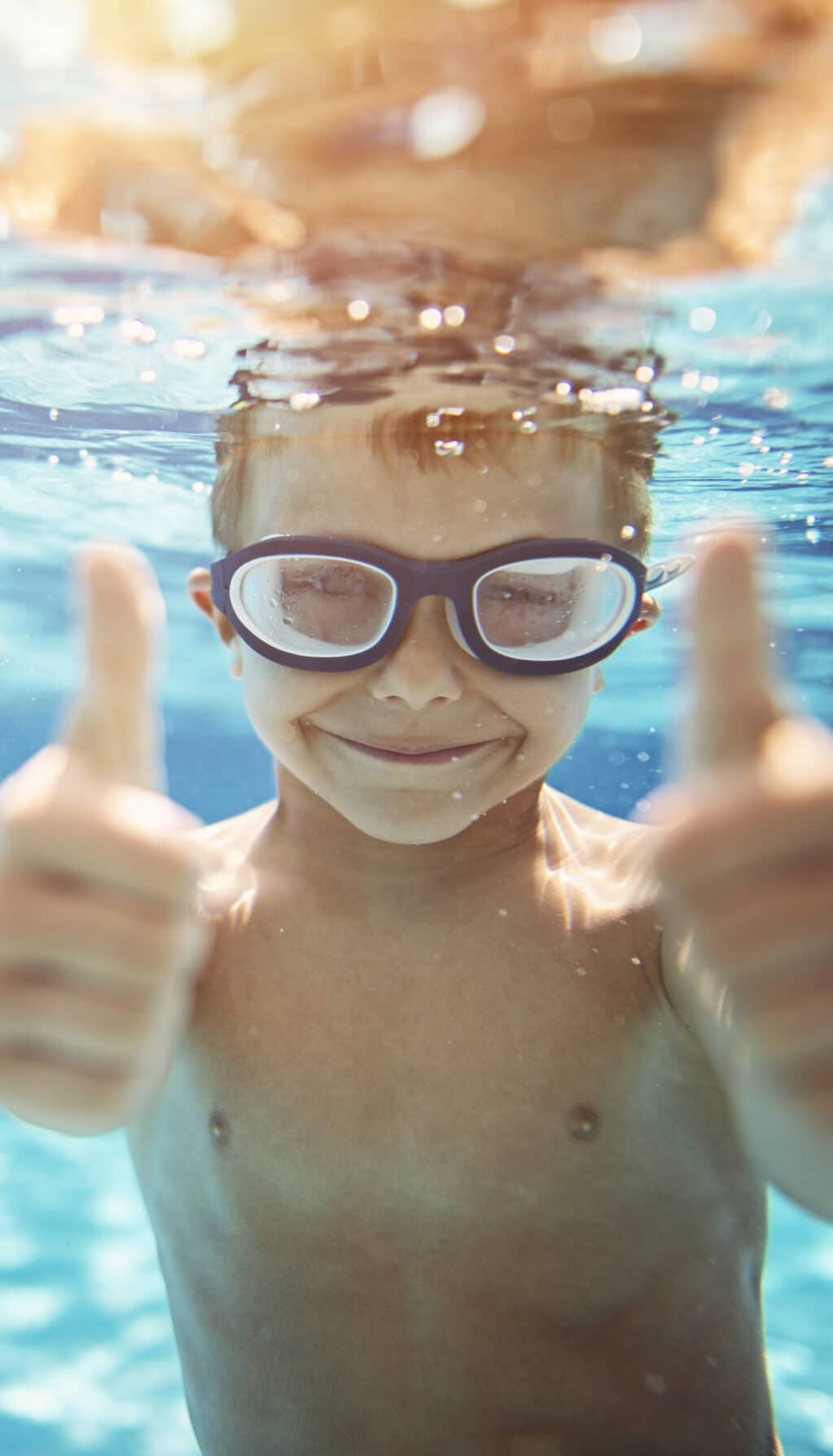 Little boy in pool showing thumbs up